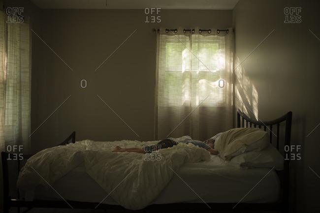 Sun coming through bedroom window with boy sleeping on bed