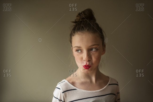 Portrait of a girl with hair in a bun and red lipstick