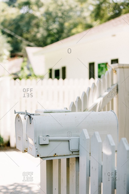 Mail boxes on a white picket fence