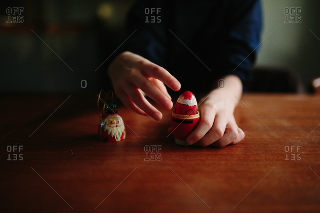 Child playing with a Santa Clause holiday ornament