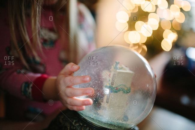 Girl shaking a holiday snow globe