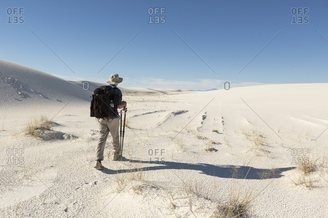 Photographer carrying equipment through White Sands National Monument, Alamogordo, New Mexico