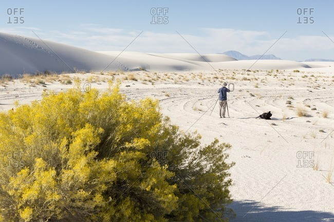 Man taking pictures of sand dunes at White Sands National Monument, Alamogordo, New Mexico