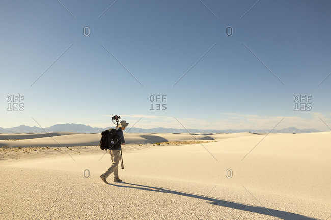Photographer walking with equipment through White Sands National Monument, Alamogordo, New Mexico
