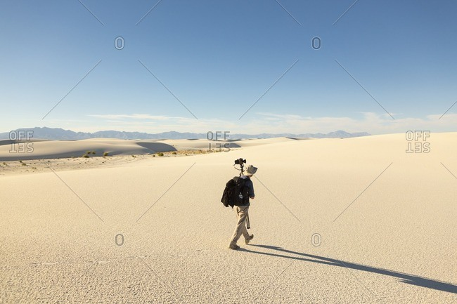 Man walking with equipment through White Sands National Monument, Alamogordo, New Mexico