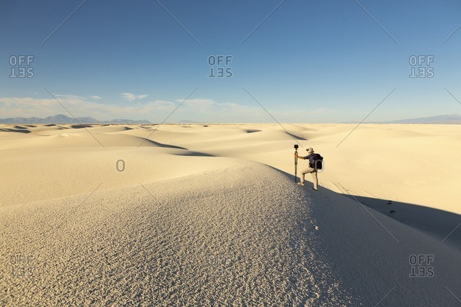 Man climbing up a sand dune with equipment at White Sands National Monument, Alamogordo, New Mexico