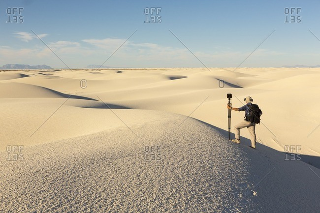 Man standing on a sand dune with equipment at White Sands National Monument, Alamogordo, New Mexico