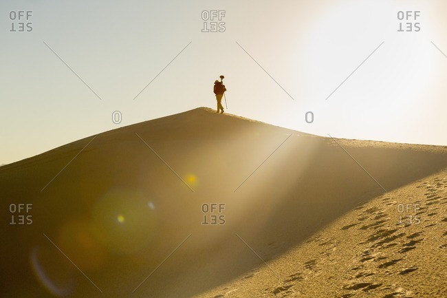 Man walking up a sand dune with equipment at White Sands National Monument, Alamogordo, New Mexico