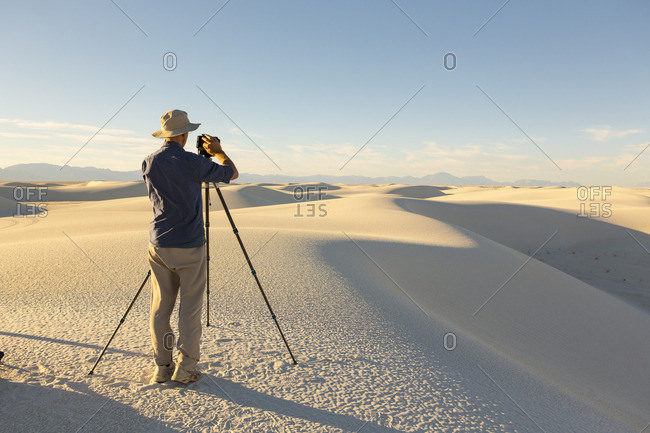 Photographer setting up camera on a tripod at White Sands National Monument, Alamogordo, New Mexico