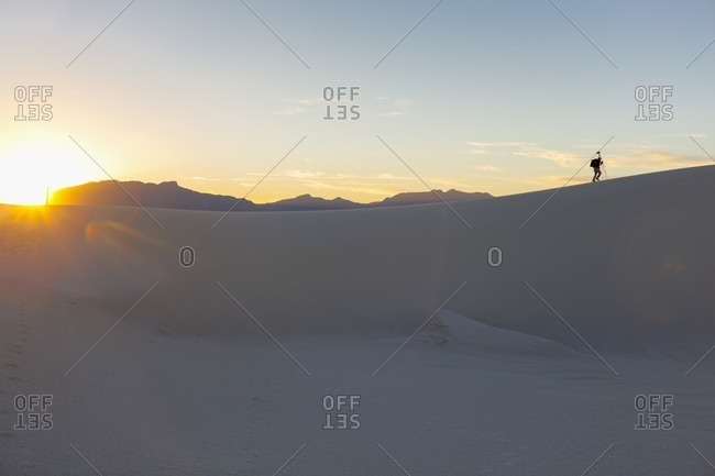 Photographer carrying equipment through White Sands National Monument at sunset, Alamogordo, New Mexico