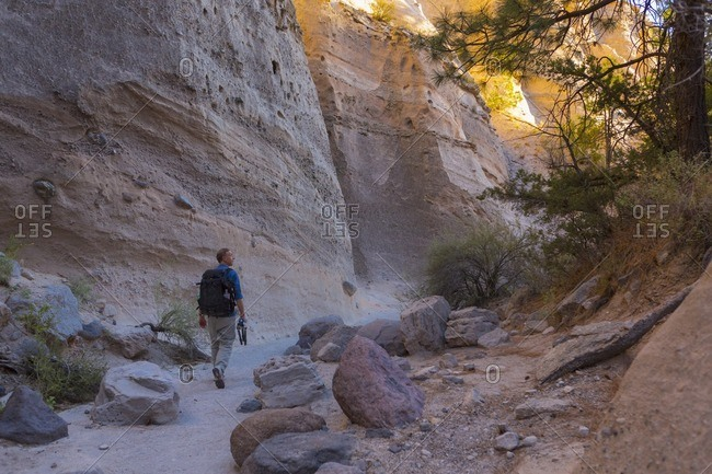 Man trekking through Kasha-Katuwe Tent Rocks National Monument with his photography gear