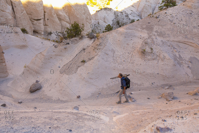 Photographer hiking with his equipment through Kasha-Katuwe Tent Rocks National Monument