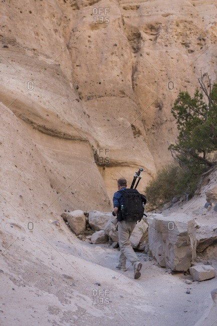Man hiking with photography equipment through Kasha-Katuwe Tent Rocks National Monument