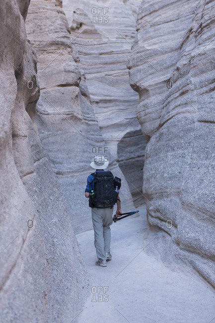 Photographer hiking through slot canyons at Kasha-Katuwe Tent Rocks National Monument