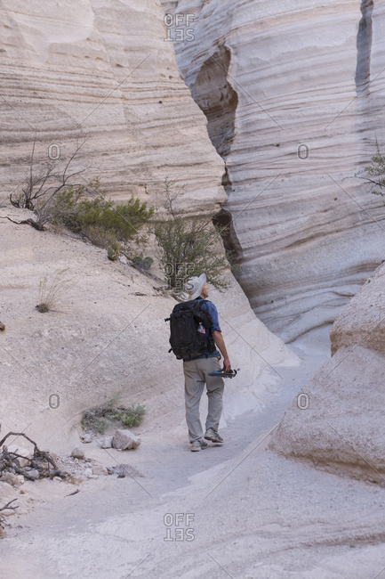 Photographer walking through Kasha-Katuwe Tent Rocks National Monument with his camera equipment