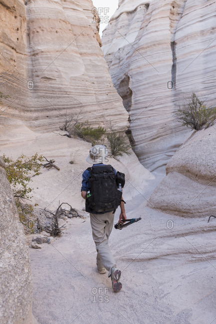 Photographer walking through Kasha-Katuwe Tent Rocks National Monument carrying equipment