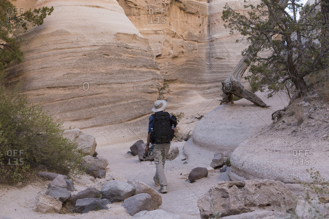 Man walking through Kasha-Katuwe Tent Rocks National Monument with photography equipment