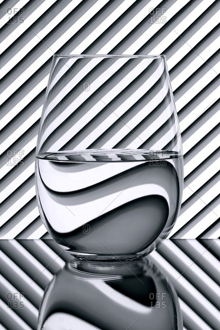 Glass of water on a striped background