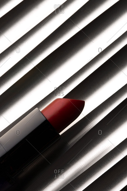 Still life of red lipstick on textured background