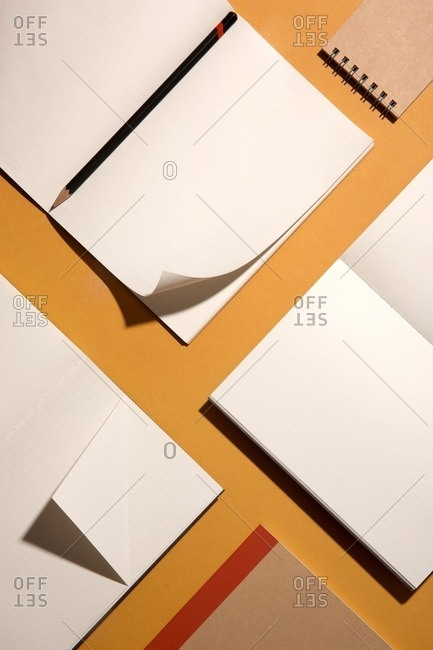 Notebooks and stationary arranged on top of yellow background