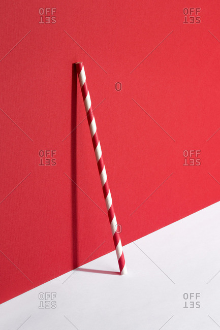 Straw leaning on red and white background