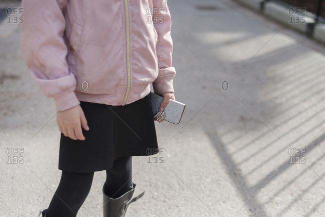 Girl (8-9) holding smart phone