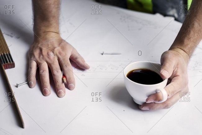 Man with coffee cup over renovation plans