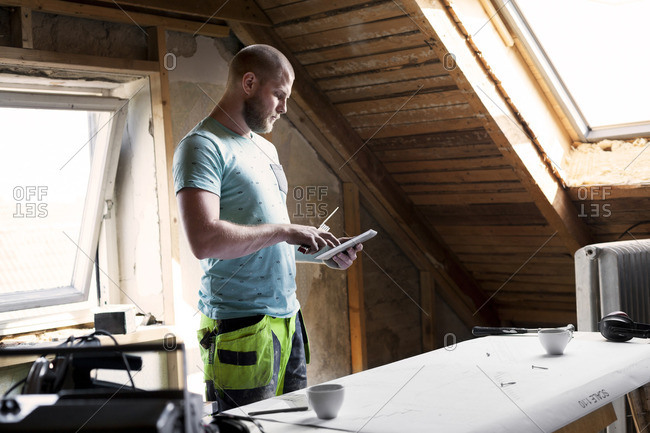 Man working on renovating old attic with tablet