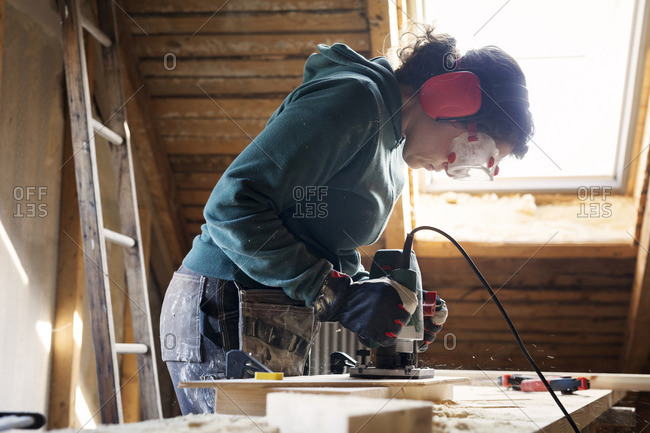 Woman using power tool while renovating old attic