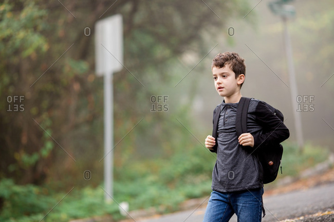 Boy on country road with backpack