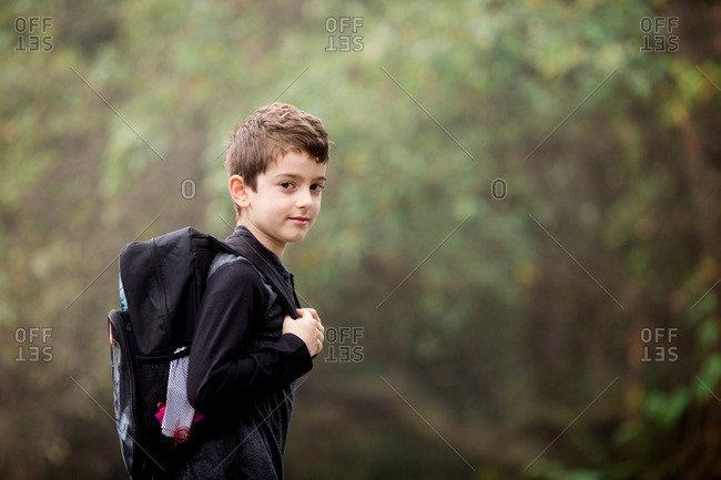 Portrait of boy in country with backpack