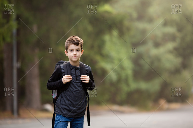 Boy in country setting with backpack