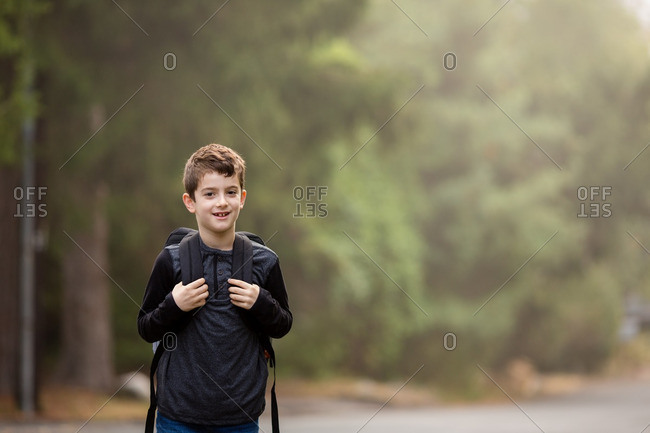 Smiling boy in county with backpack