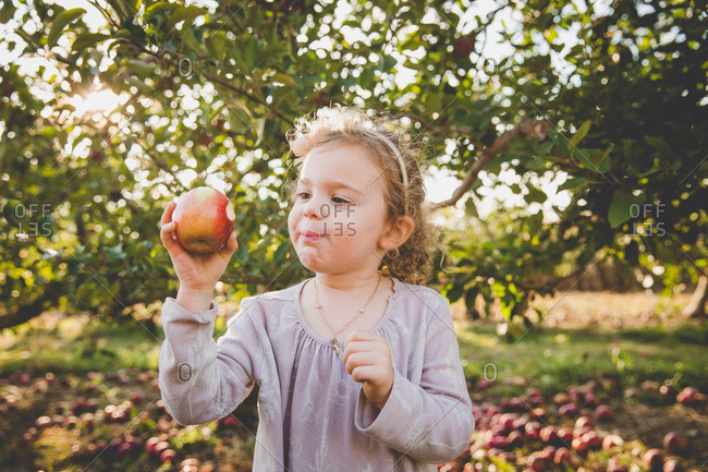 Girl taking bite of fresh picked apple