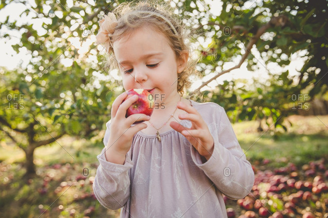 Girl taking bite of a fresh picked apple