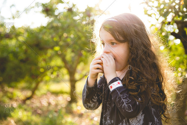 Young girl biting into fresh apple