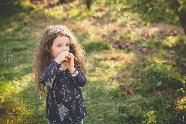 Young girl biting into a fresh apple