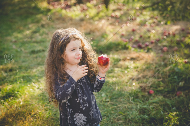 Girl smiling while eating apple