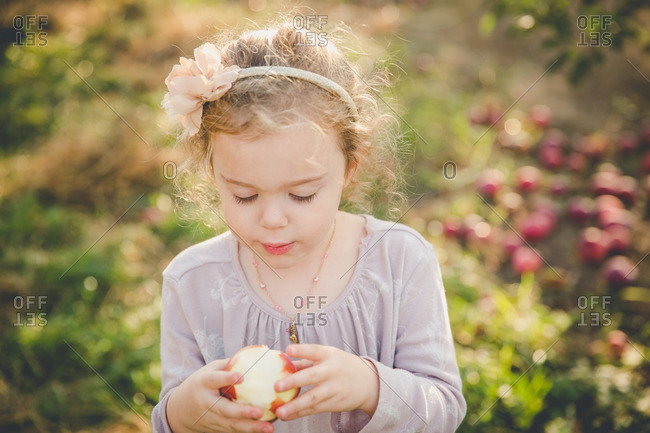 Girl looking at fresh picked apple