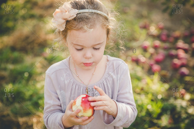 Girl looking at a fresh picked apple