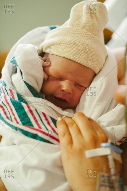 Mom holding swaddled newborn