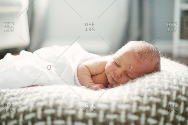 A newborn sleeping on a soft pillow