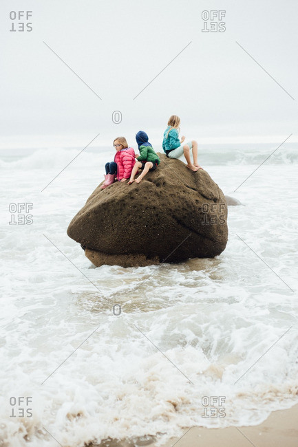 Three children on a large rock surrounded by incoming tide on the beach