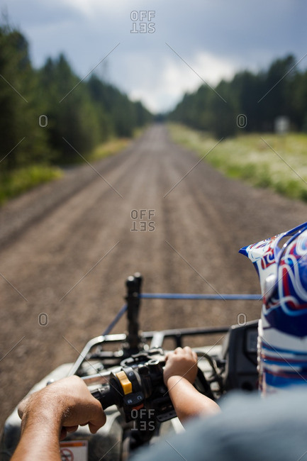 Boy riding four-wheeler with his dad on a long dirt road