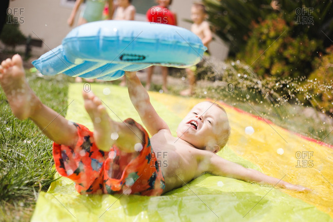 Little boy slipping on plastic slide with a look of distress