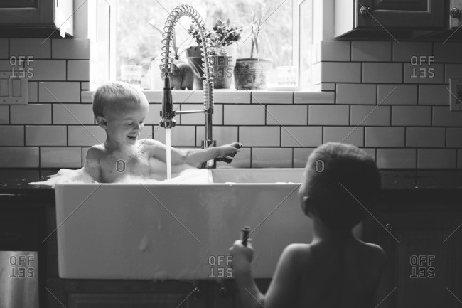 Young boy watches his brother taking a bath in a sink