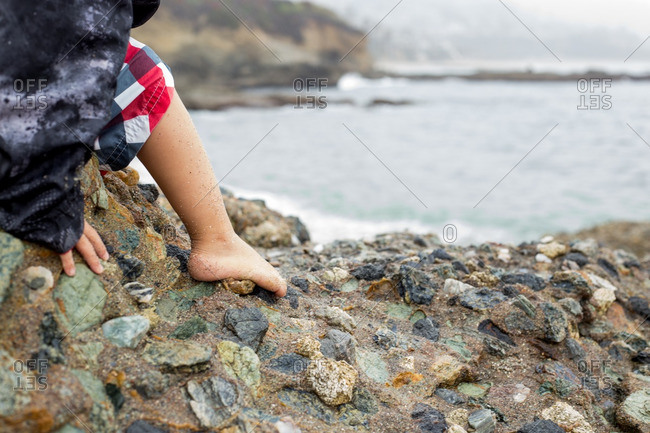 Little boy sitting on a large rock made up of many smaller rocks on the beach
