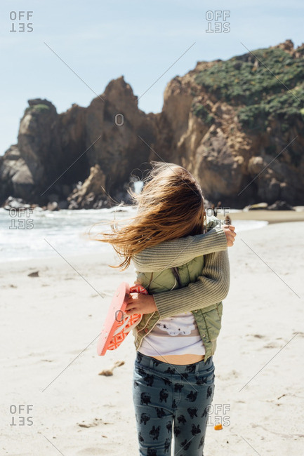 Young girl in a jacket standing on a beach shielding her face from the wind