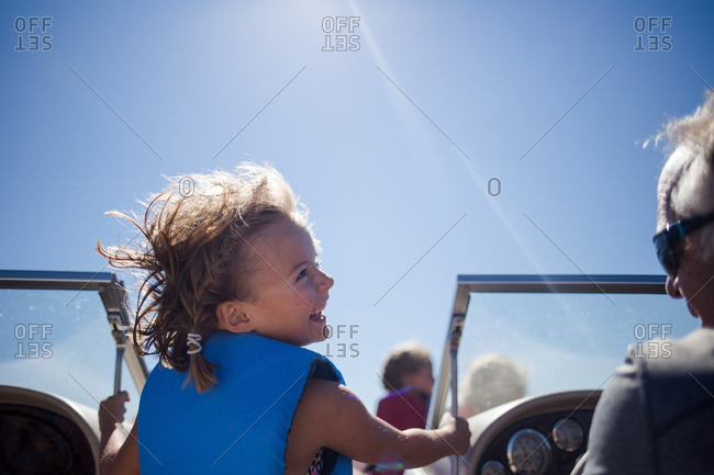 Happy young girl on boat laughing at grandfather