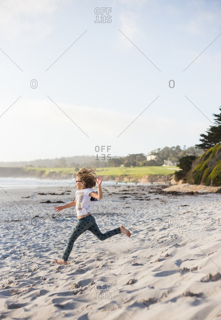 Young girl running down the beach towards the ocean